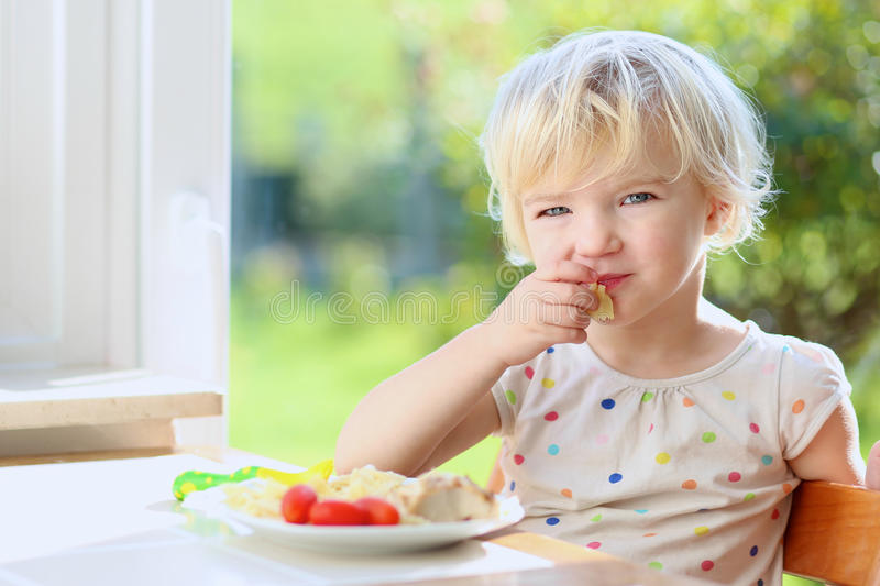 Little girl eating pasta for lunch royalty free stock image