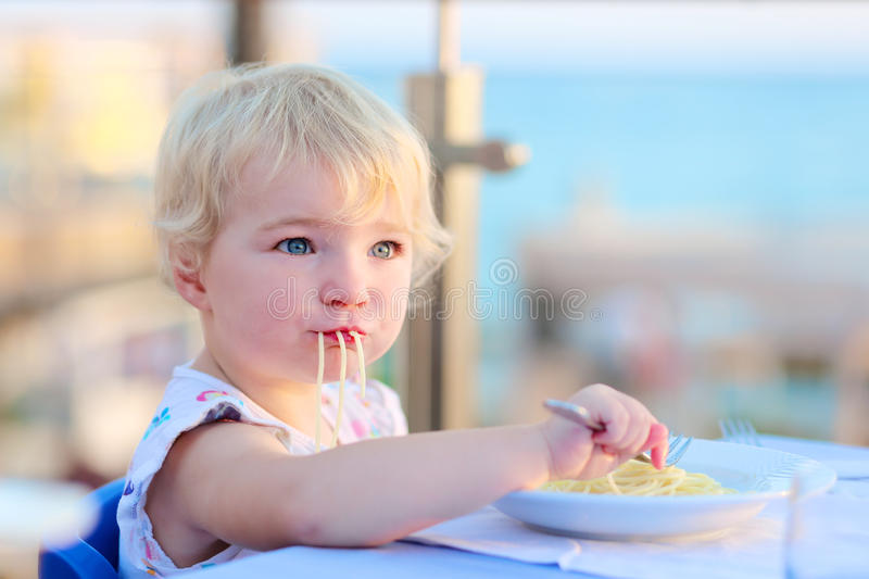 Little girl eating pasta at restaurant. Happy healthy little child, cute blonde toddler girl, enjoying summer vacation in tropical resort eating pasta at beach royalty free stock photo