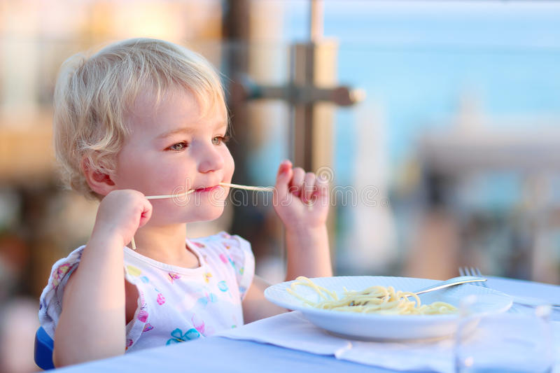 Little girl eating pasta at restaurant. Happy healthy little child, cute blonde toddler girl, enjoying summer vacation in tropical resort eating pasta at beach royalty free stock images