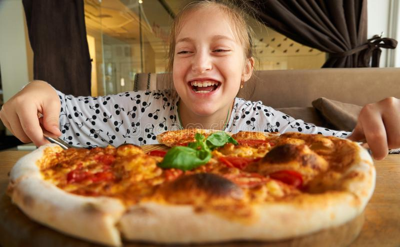 Little girl eating pizza and having fun, sitting on sofa in city cafe stock photos