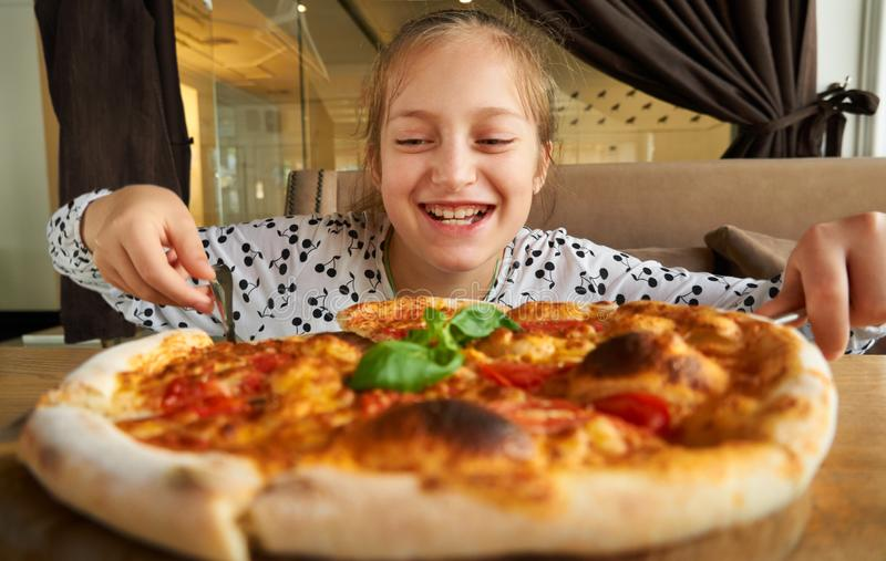 Little girl eating pizza and having fun, sitting on sofa in city cafe stock photography