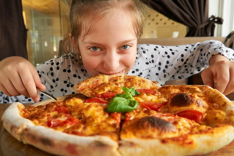 Little girl eating pizza and having fun, sitting on sofa in city cafe royalty free stock photo