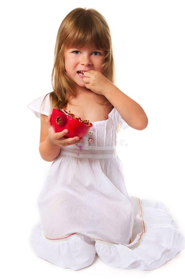 Little girl eating pomegranate royalty free stock photo