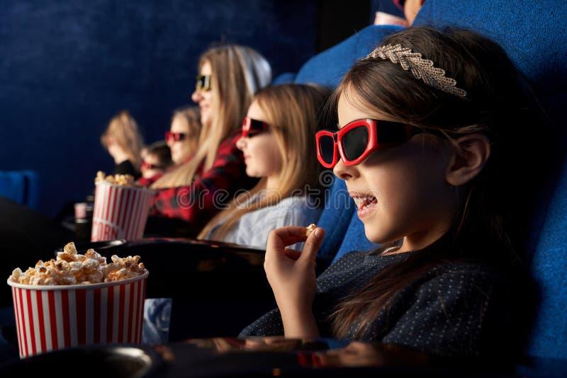 Little girl eating popcorn, watching cartoon in cinema. royalty free stock photo