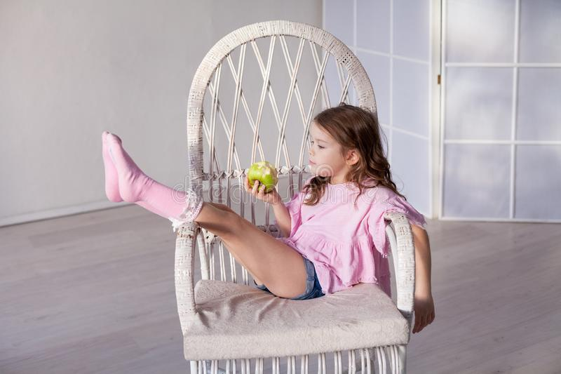 Little girl eating ripe Green Apple healthy food royalty free stock photos