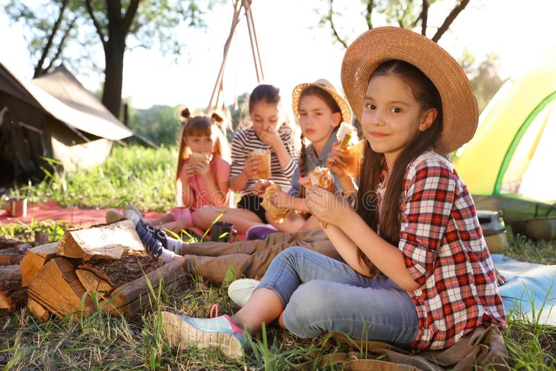Little girl eating sandwich outdoors. Summer camp stock images