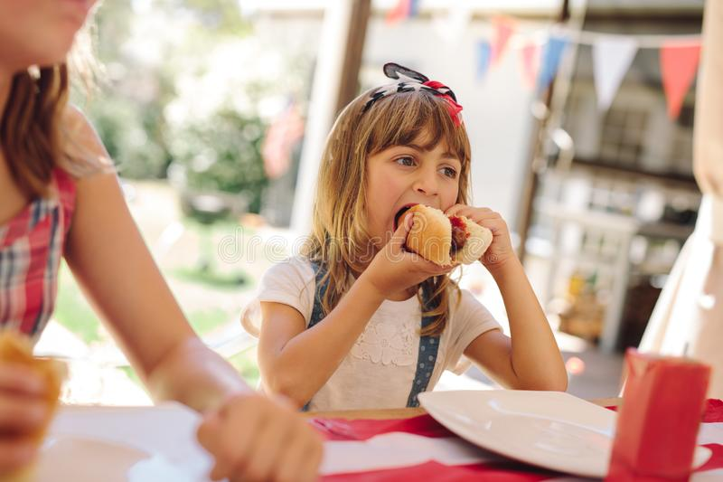 Little girl eating snacks at a restaurant stock photography