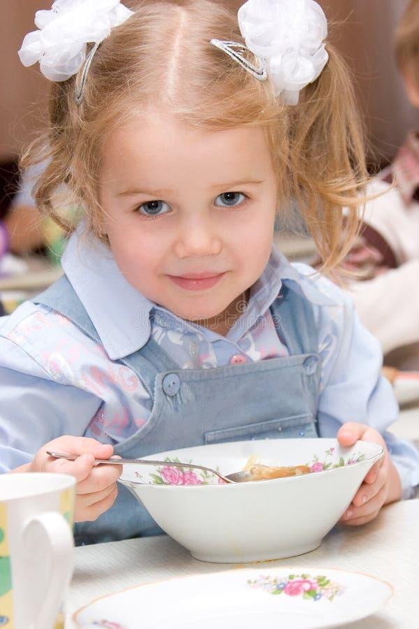 Little girl eating soup. Adorable little girl eating soup stock photo
