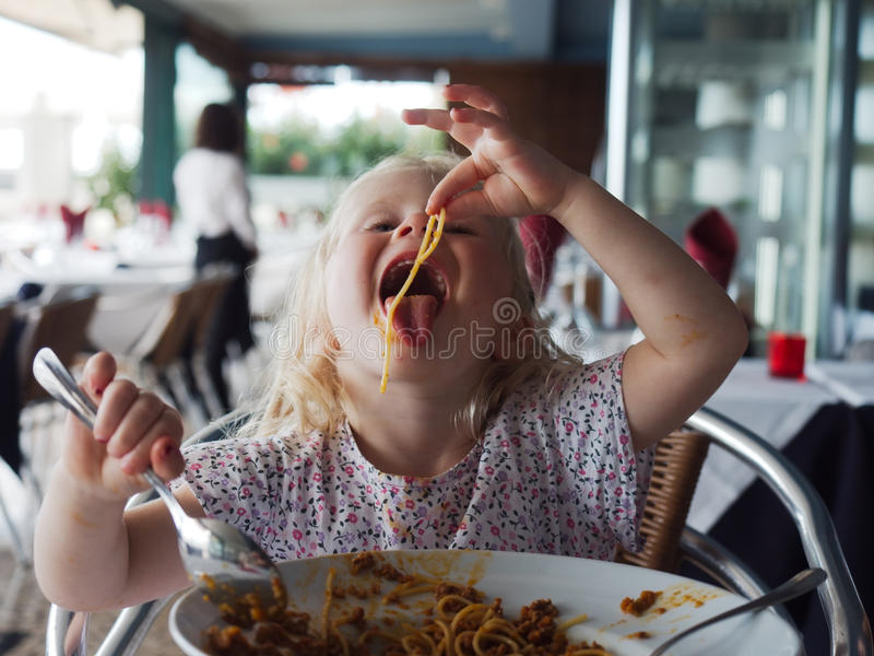 Little girl eating spaghetti royalty free stock photography