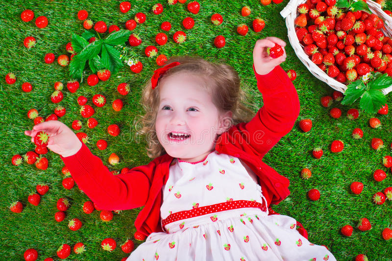 Little girl eating strawberry. Child eating strawberry. Little girl playing peek a boo holding fresh ripe strawberries. Kids eating fruit relaxing on a lawn stock image