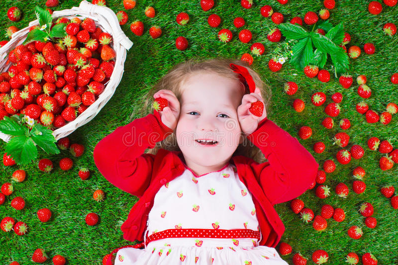 Little girl eating strawberry. Child eating strawberry. Little girl playing peek a boo holding fresh ripe strawberries. Kids eating fruit relaxing on a lawn stock photos
