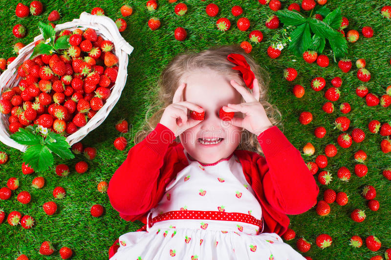 Little girl eating strawberry. Child eating strawberry. Little girl playing peek a boo holding fresh ripe strawberries. Kids eating fruit relaxing on a lawn stock images
