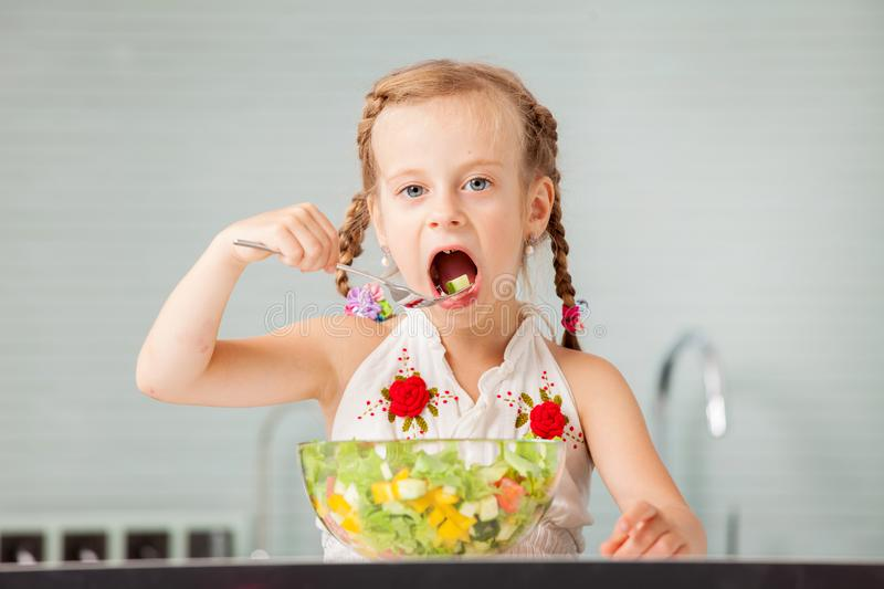 Little girl eating vegetable salad. In the kitchen. Child at home royalty free stock image