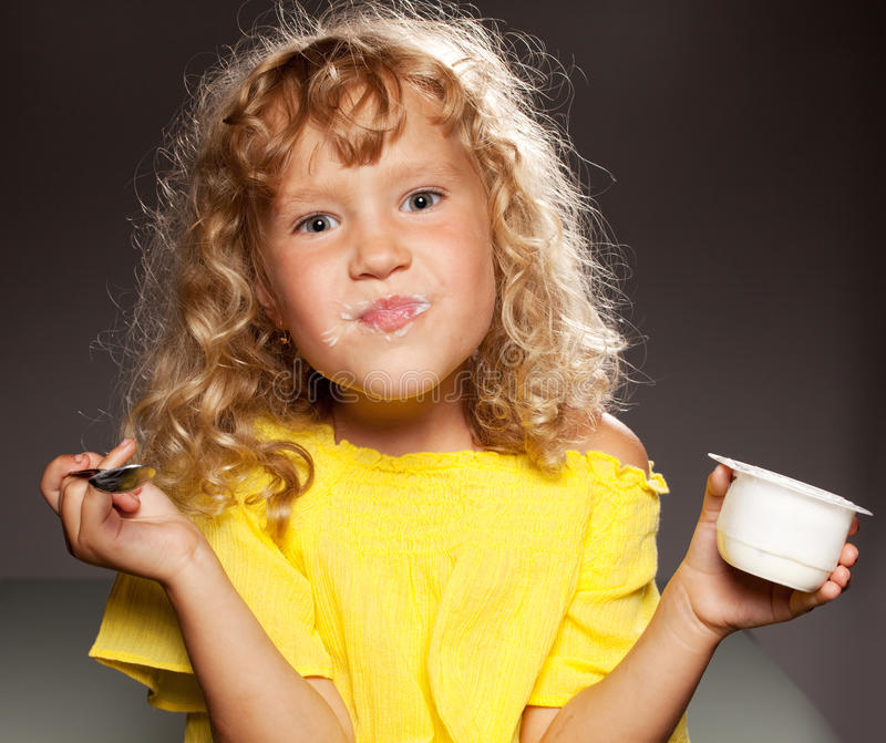Download Little girl eating yogurt stock image. Image of emotions - 21110587