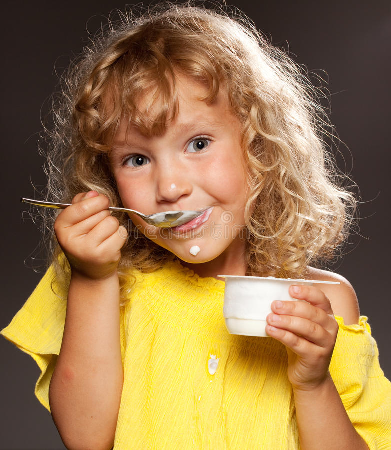 Download Little girl eating yogurt stock image. Image of expressions - 22317089