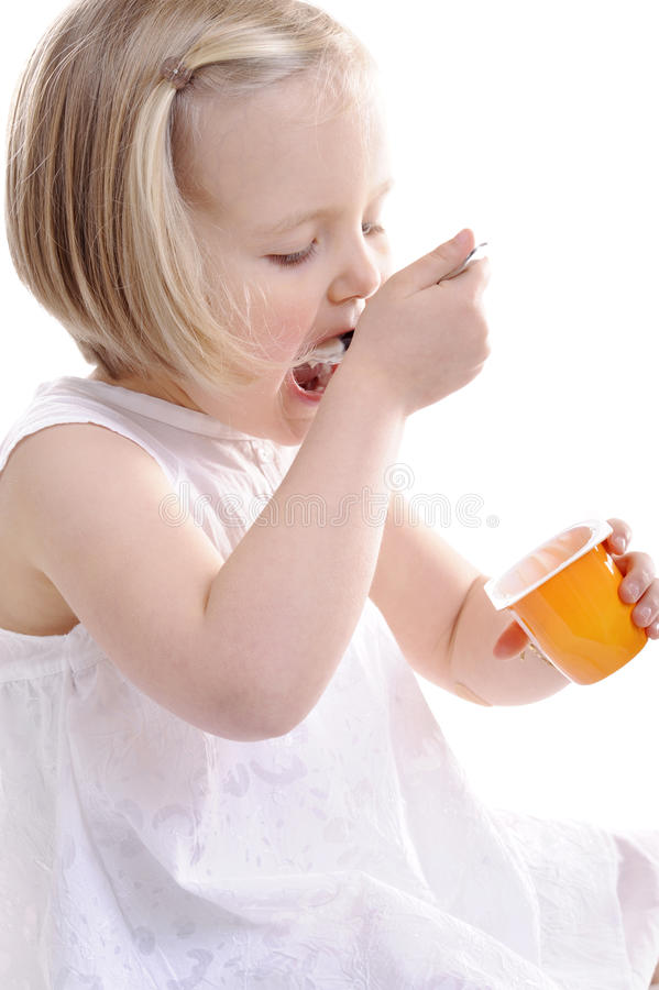 Little girl eating yogurt, mouth wide open stock photo