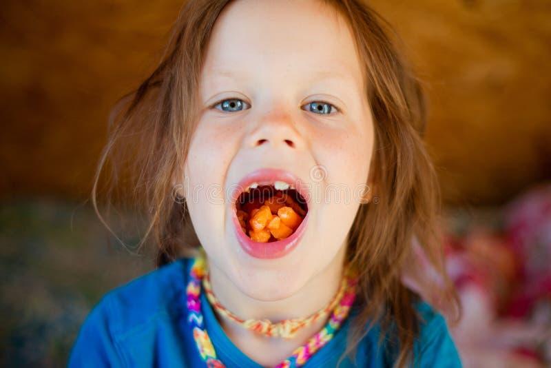 Little girl eats a carrot.  stock photos