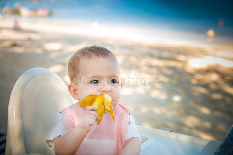 A little girl eats a delicious banana on a tropical sandy beach. The baby meets with food. The development of fine motor skills.  royalty free stock image