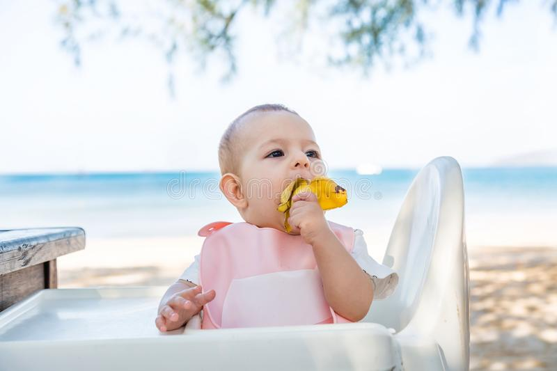 A little girl eats a delicious banana on a tropical sandy beach. The baby meets with food. The development of fine motor skills. Sea on background stock photo