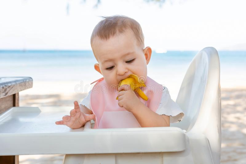 A little girl eats a delicious banana on a tropical sandy beach. Looking down. The baby meets with food. The development of fine royalty free stock photography