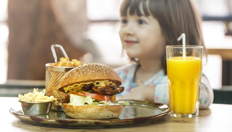 Little girl eats in a fast food cafe royalty free stock photo