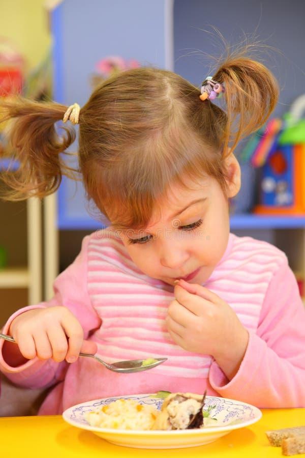 Little girl eats in kindergarten stock photography