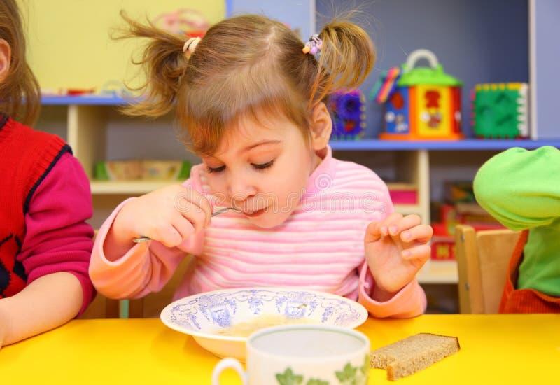 Little girl eats in kindergarten royalty free stock photography