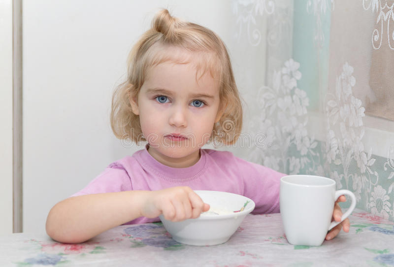Little girl eats porridge from sitting at the table. royalty free stock images