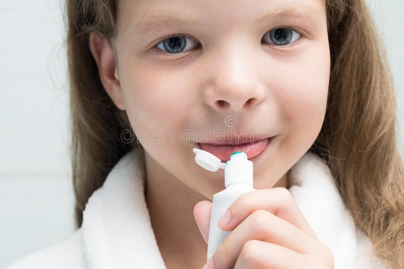 Little girl eats white toothpaste, closeup view. Little girl eats white toothpaste,  closeup view royalty free stock photography