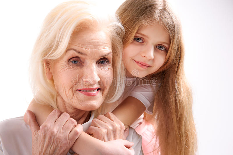Little girl with elder relative. Small granddaughter is hugging her grandmother. They are glancing at camera with happiness in their eyes. . Portrait stock images