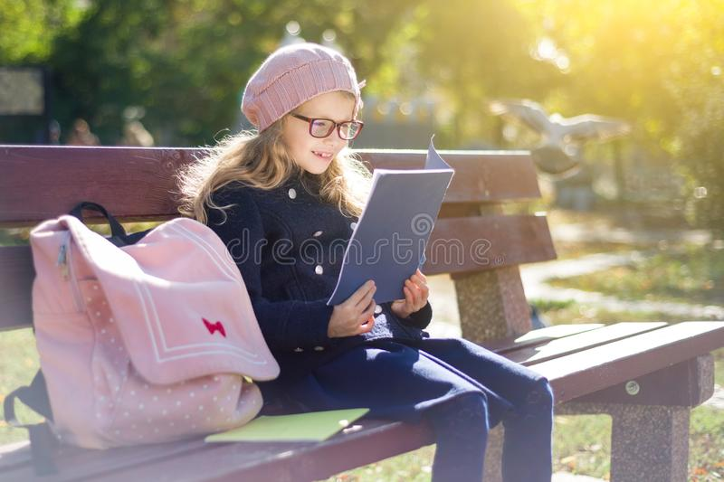 Little girl elementary school student sitting on bench with backpack, looks at school books and notebooks. stock images