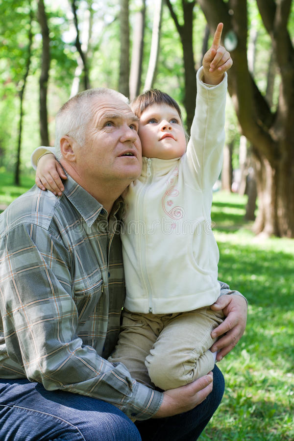 Little girl embraces grandfather, sits on arms and royalty free stock image