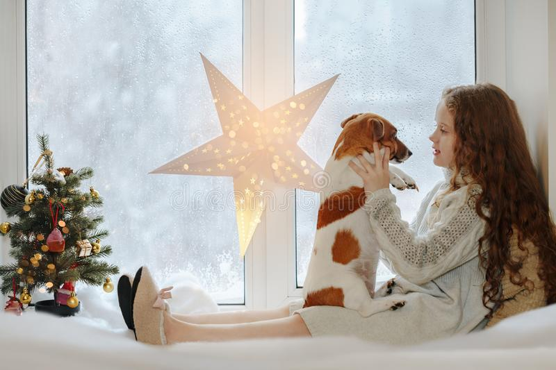Little girl embracing her puppy dog, sitting on window and waiti stock photo