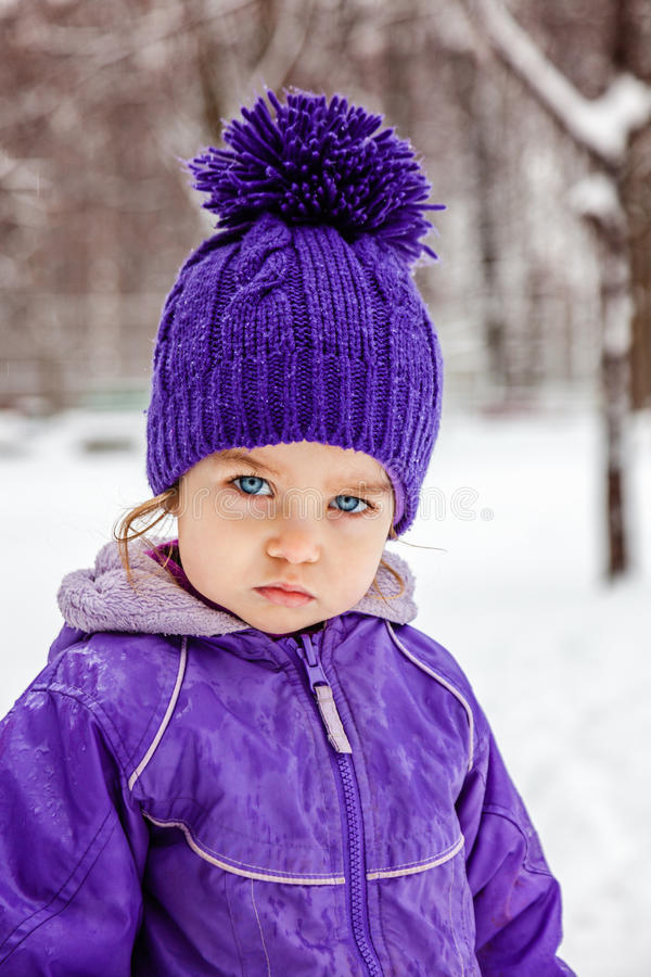 Little girl emotional portrait, closeup. Kid looking straight into the camera. Child walking outside. royalty free stock photography