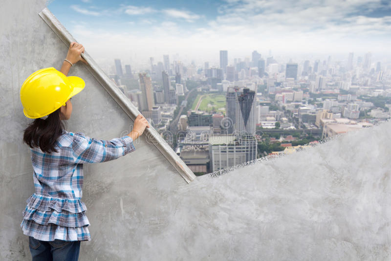Little girl engineering holding plastering tools painting skyscraper on wall. Little girl engineering ideas concept with hand holding plastering tools renovating royalty free stock image