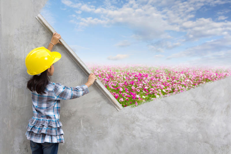 Little girl engineering with painting flowers grass on wall. Little girl engineering ideas concept with hand holding plastering tools renovating a house. With royalty free stock photo
