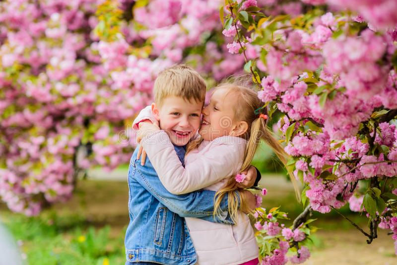 Little girl enjoy spring flowers. Giving all flowers to her. Surprising her. Kids enjoying pink cherry blossom. Romantic stock photography