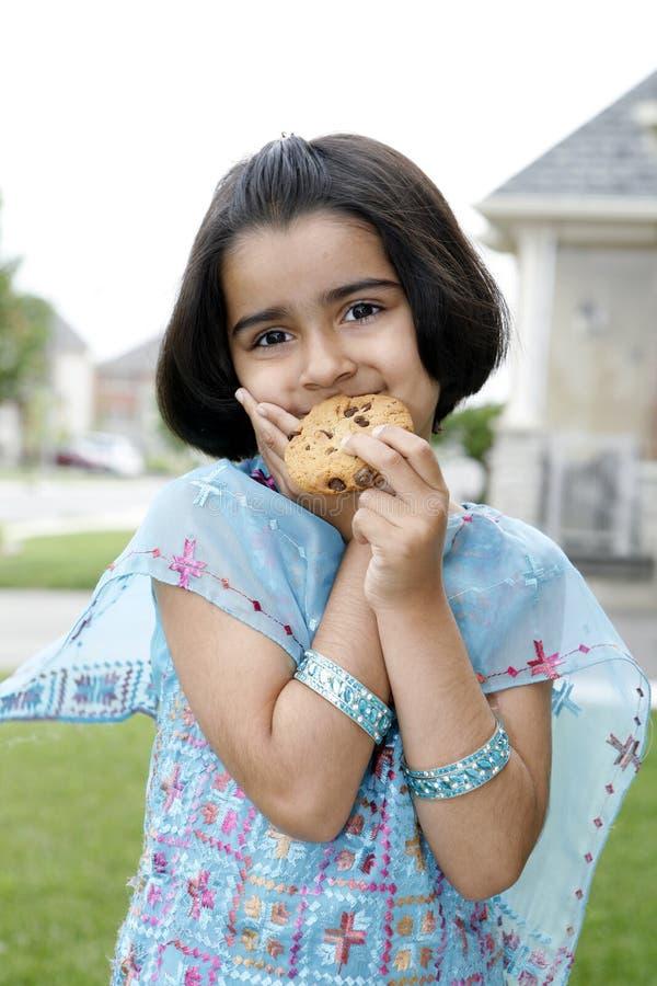 Download Little Girl Enjoying Cookie Stock Photo - Image: 5726438
