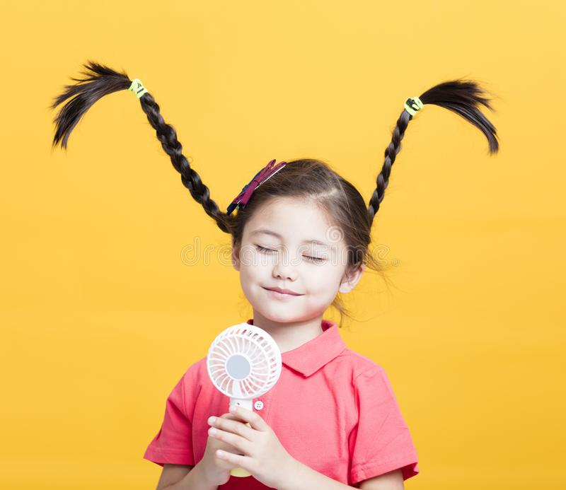 Little girl enjoying cool wind from electric fan stock photography