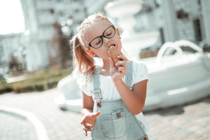 Little girl enjoying her ice-cream cone in summer. stock photo
