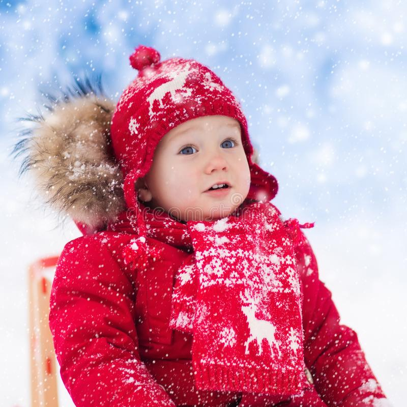 Kids play in snow. Winter sleigh ride for children. Little girl enjoying a sleigh ride. Child sledding. Toddler kid riding a sledge. Children play outdoors in royalty free stock photography