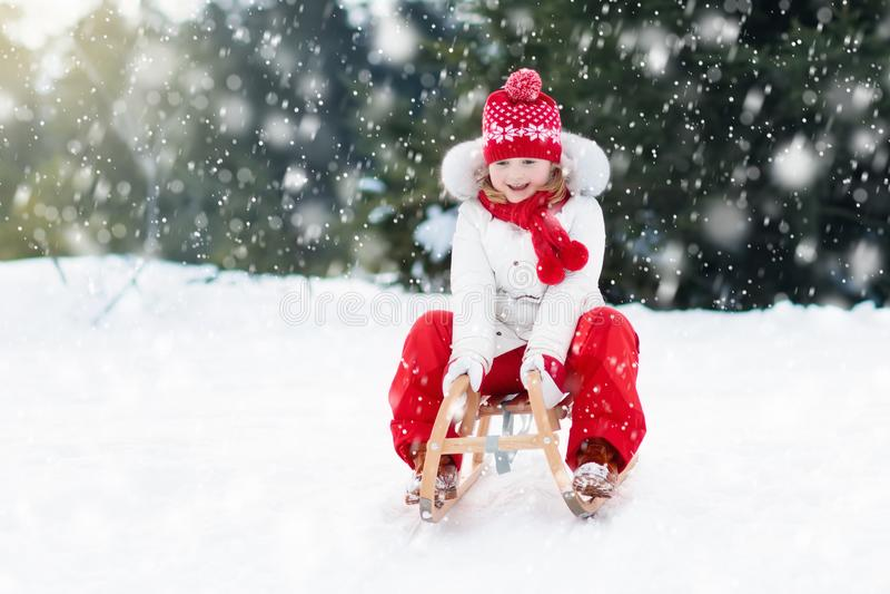 Child sledding. Kid with sledge. Winter snow fun. stock photography