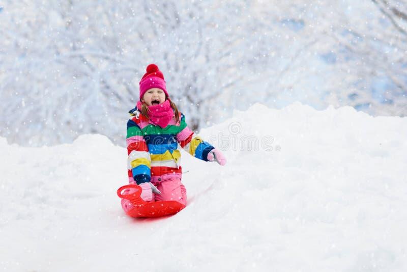 Girl on sled ride. Child sledding. Kid on sledge. Little girl enjoying a sleigh ride. Child sledding. Toddler kid riding a sledge. Children play outdoors in snow stock image