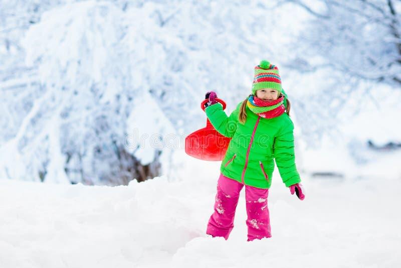 Girl on sled ride. Child sledding. Kid on sledge. Little girl enjoying a sleigh ride. Child sledding. Toddler kid riding a sledge. Children play outdoors in snow stock images