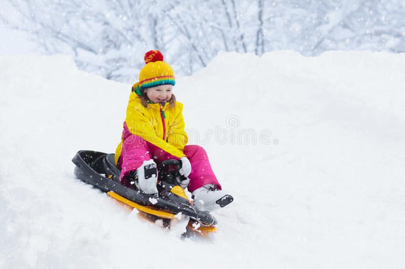 Little girl enjoying a sleigh ride. Child sledding. Toddler kid riding a sledge. Children play outdoors in snow. Kids sled in the royalty free stock photo