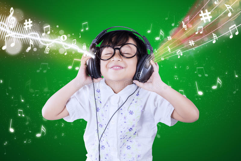 Little girl enjoys the music melody. Portrait of cute little girl using headphones to listen the music melody stock photography