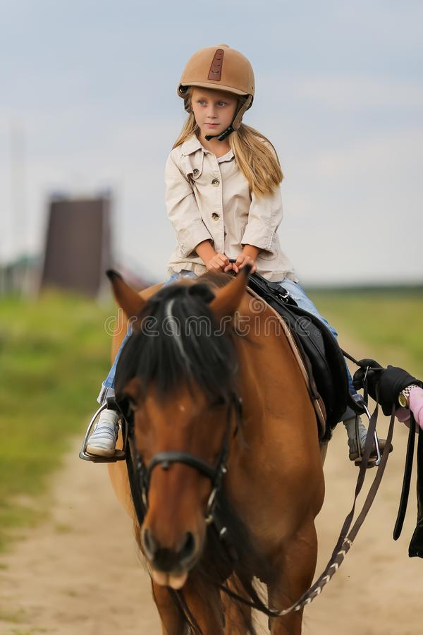 Little girl in equestrian helmet riding a horse. Little girl in equestrian helmet riding horse royalty free stock image