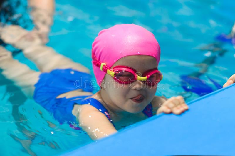 A little girl of European appearance in glasses in the pool, shows the language and looking at the camera royalty free stock photo