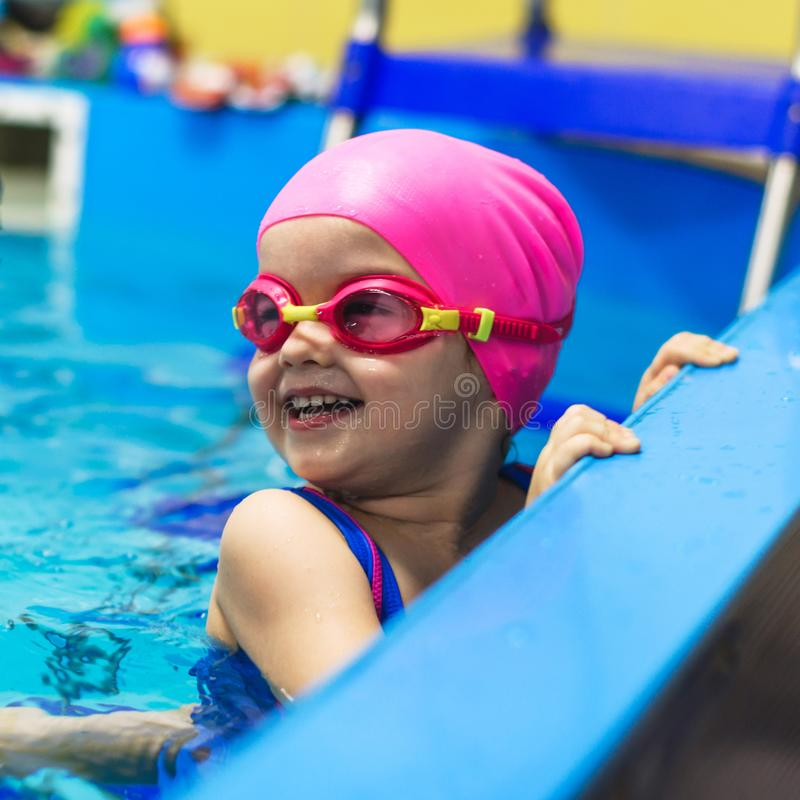 A little girl of European appearance in glasses in the pool, smiling and looking at camera royalty free stock image