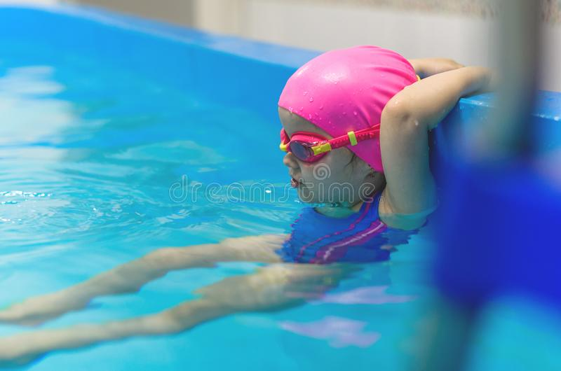 A little girl of European appearance in a pink rubber cap learning to swim in the pool stock image